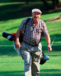 Picture of an elderly man with his golf clubs