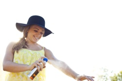 Teen girl wearing a wide-brimmed hat and spraying sunscreen on her arm