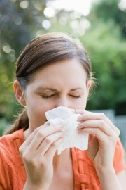 Photo of a woman sneexing into a tissue