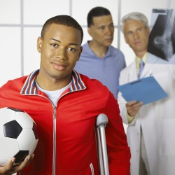 Teen carrying a soccer ball and resting on a crutch at doctor's office
