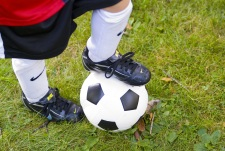 Child's foot on top of a soccer ball