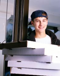 Young man holding pizza boxes