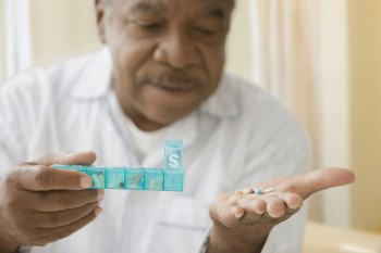 Middle aged man is holding a pill organizer in one hand and is looking at the pills in his other hand.