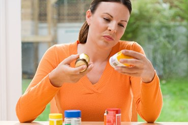 Woman is holding two pill bottles and reading the label on one of the bottles.