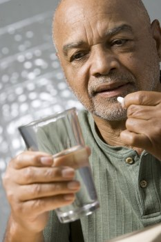 Photo of a middle aged man holding a glass of water in one hand and  a pill in the other hand. He is getting ready to take the pill.