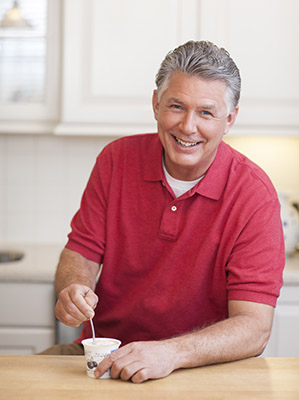 Man eating yogurt in the kitchen