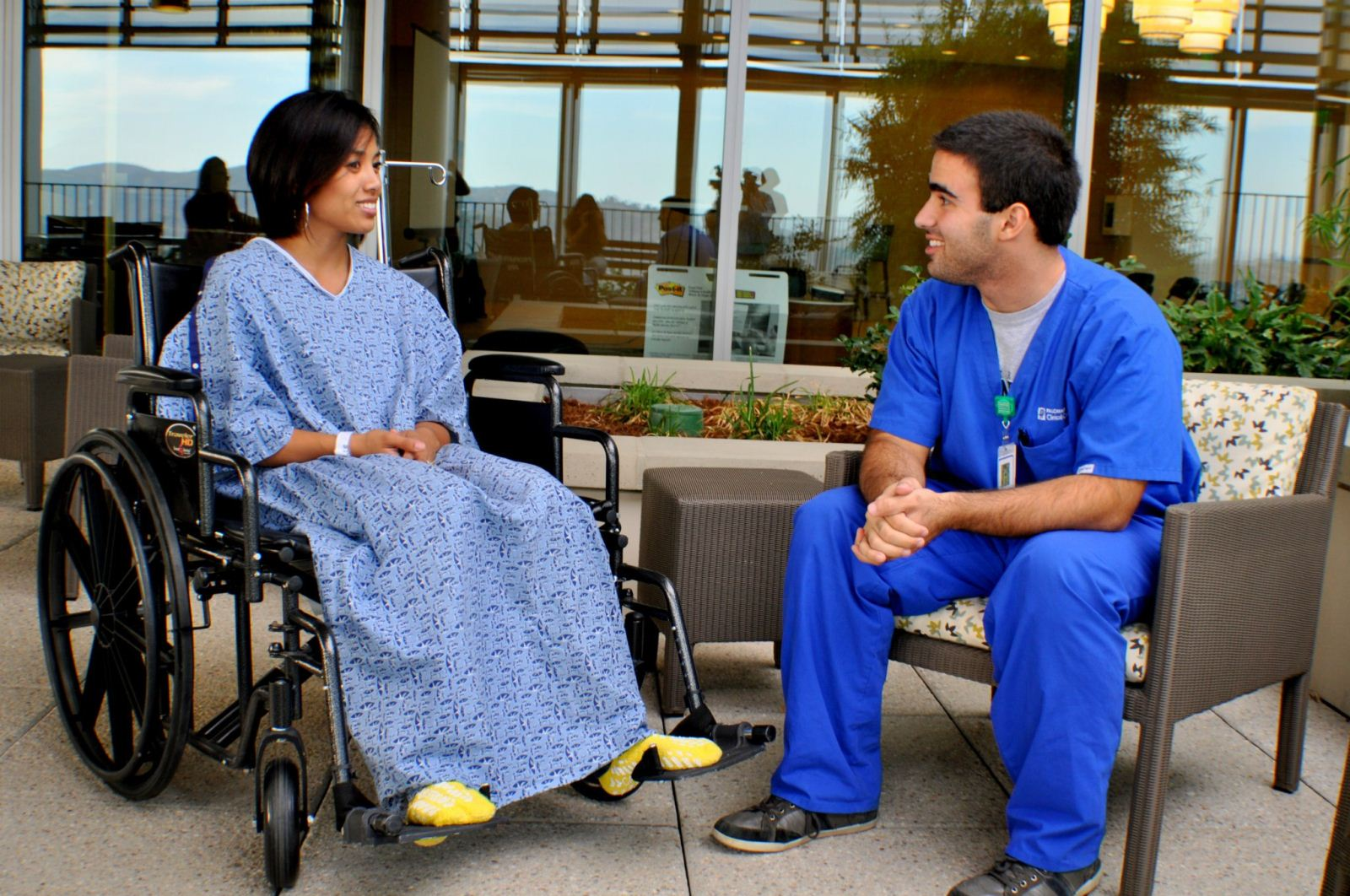 A intern talks to a patient in a hospital environment.